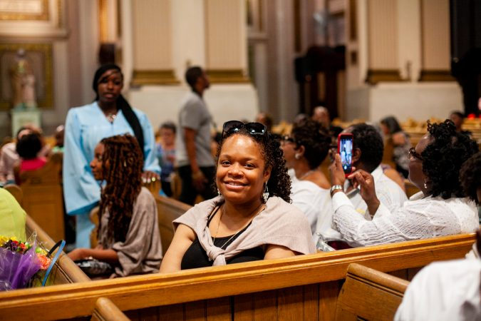 Gesu School parent Eboni Scott sits in the chapel of the Church of the Gesu before the school's graduation ceremony earlier this month. (Brad Larrison for WHYY)