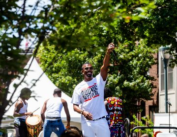 Host of the Odunde Festival Six King hypes up the crowd on South Street Sunday during the festival celebrating African and Carribean culture. (Brad Larrison for WHYY)