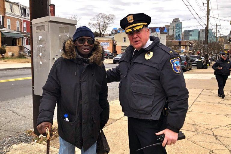 Wilmington Police Chief Robert J. Tracy with resident Robert Flonnory on Market Street. Tracy has been credited with bringing down the crime rate in the city by building bridges within communities. (Cris Barrish/WHYY)