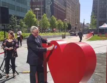 Mayor Jim Kenney puts his flag of family origin on the new sculpture at Love Park. (Tom MacDonald/WHYY)