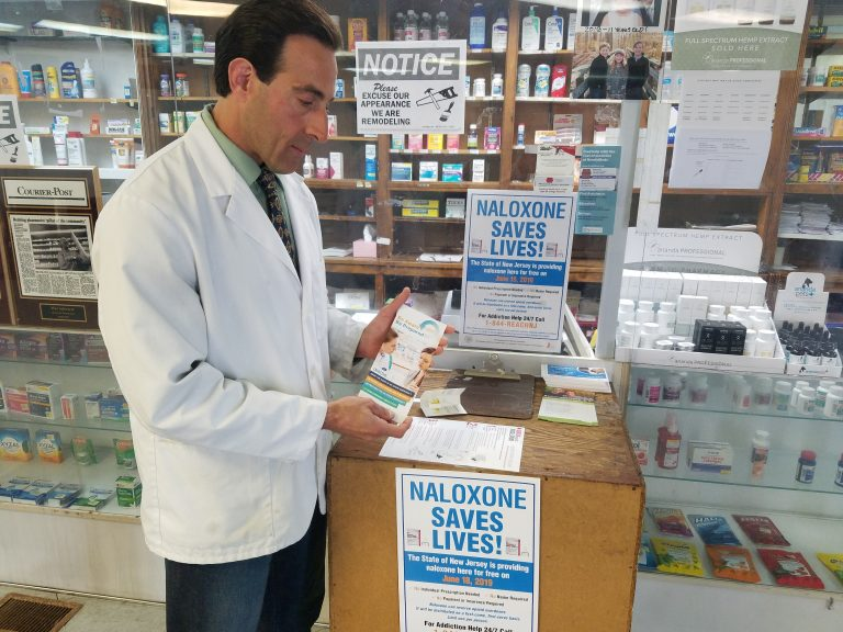 Anthony Minniti, a pharmacist and the owner of Bell Pharmacy in Camden, displays some of the educational material he handed out to people claiming free doses of naloxone on Tuesday, June 18, 2019. (Nicholas Pugliese/WHYY)