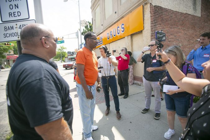 Camden business owner Todd Israel speaks about his experience owning a business in Camden during a group tour of the city (Miguel Martinez for WHYY)