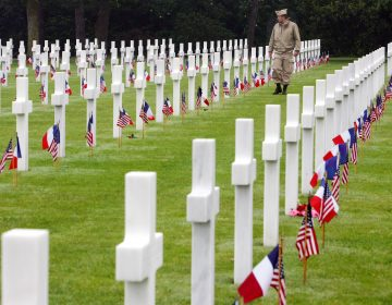 A visitor wearing a U.S. military uniform walks past graves at the American cemetary, in Colleville-sur-Mer, western France, in this June 6, 2007 file photo. (Remy de la Mauviniere/AP Photo)
