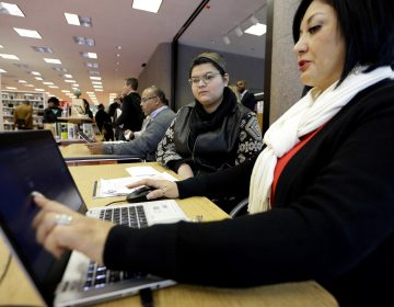 In this Friday, Nov. 14, 2014 file photo, Affordable Care Act health insurance marketplace navigator Leticia Chaw, right, helps gather information for Jennifer Sanchez to re-enroll in a health insurance plan in Houston. (David J. Phillip/AP Photo)