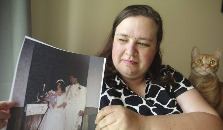"""Heidi Clark holds a photograph from her 1995 wedding at her home in Orem, Utah, on Friday, May 18, 2018. Clark became pregnant at 16 and married soon after, under pressure from her boyfriend's religious community of Seventh-Day Adventists in Pennsylvania, she said. """"I always felt a little bit like I was trapped,"""" Clark said, now 40. """"I was 17. I was so young."""" (Rick Bowmer/AP Photo)"""
