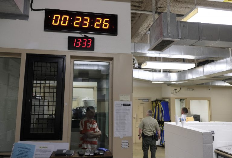 A clock at top counts down intervals between checks on inmates in the booking area holding cells at the Lake County Jail in Lakeport, Calif., on Tuesday, April 16, 2019. Major reforms were put in place at the jail following the 2015 suicide of a woman with a history of mental health problems who had repeatedly begged for help. Her son's lawsuit resulted in $2 million wrongful death settlement. (AP Photo/Eric Risberg)