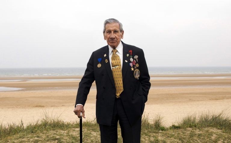 World War II and D-Day veteran Charles Norman Shay, from Indian Island, Maine, poses on a dune at Omaha Beach in Saint-Laurent-sur-Mer, Normandy, France, Wednesday, May 1, 2019. Shay was a combat medic on D-Day, assigned to an assault battalion in the first wave of attacks on D-Day, June 6, 1944. (Virginia Mayo/AP Photo)