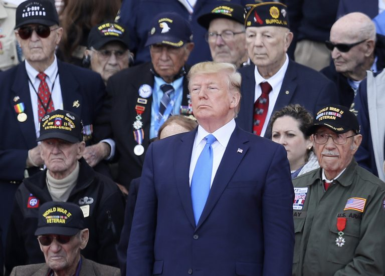 U.S. President Donald Trump stands with World War II veterans during a ceremony to mark the 75th anniversary of D-Day at the Normandy American Cemetery in Colleville-sur-Mer, Normandy, France, Thursday, June 6, 2019. World leaders are gathered Thursday in France to mark the 75th anniversary of the D-Day landings. (David Vincent/AP Photo)