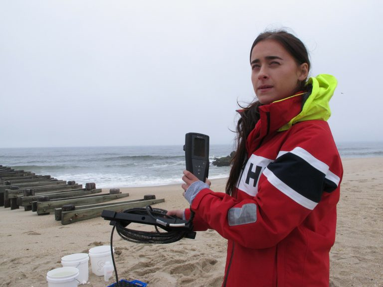 This May 30, 2019 photo shows Skye Post, who will be a junior at Monmouth University this fall, demonstrating water quality testing equipment near a storm drain outfall pipe on the beach in Long Branch, N.J. University researchers are studying the relationship between heavy rainfall and elevated levels of bacteria from animal waste that gets flushed into storm sewers and out in the ocean at popular surfing beaches at the Jersey shore. (Wayne Parry/AP Photo)