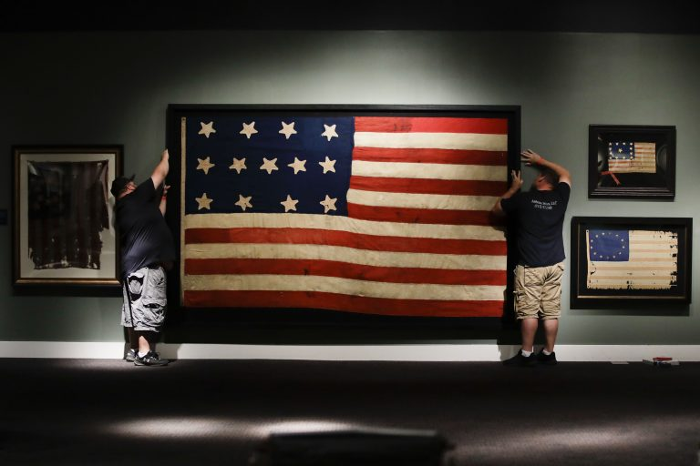 In this Wednesday, June 12, 2019 photo, workmen hang a Federal Era flag as part of the new exhibit 'A New Constellation: A Collection of Historic 13-Star Flags,' at the Museum of the American Revolution in Philadelphia. (Matt Rourke/AP Photo)