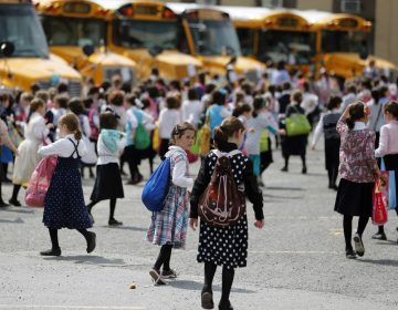 In this July 1, 2014 file photo, Orthodox Jewish girls walk to waiting buses after summer day camp in Kiryas Joel, N.Y. Kiryas Joel is a tightly packed Hasidic enclave surrounded by suburbia in the Hudson Valley. As a measles outbreak stretches toward summer camp season, New York counties with a concentration of Orthodox Jewish camps are requiring vaccinations for campers and staff. (Mike Groll/AP Photo)
