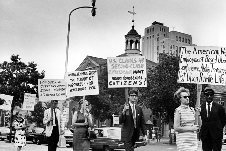FILE - In this July 4, 1967 file photo Kay Tobin Lahusen, right, and other demonstrators carry signs calling for protection of homosexuals from discrimination as they march in a picket line in front of Independence Hall in Philadelphia. In 2019, same-sex marriage is the law of the land in the U.S. and at least 25 other countries. LGBT Americans serve as governors, big-city mayors and members of Congress, and one _ Pete Buttigieg _ is waging a spirited campaign for president. (AP Photo/John F. Urwiller)