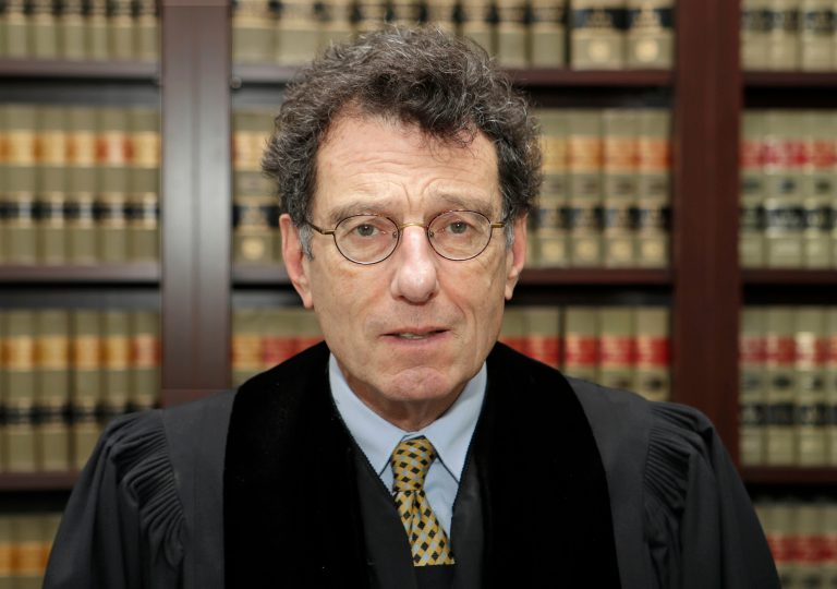 In this Jan. 11, 2018, file photo, U.S. District Judge Dan Polster poses for a portrait in his office in Cleveland. Polster is holding a hearing Tuesday, June 25, 2019,  in Cleveland on a plan pitched by lawyers for local governments on distributing money to nearly 25,000 municipal and county governments. The plan would take effect if companies that make and distribute the powerful prescription painkillers agree to one or more legal settlements. (Tony Dejak/AP Photo)