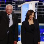 Democratic presidential candidates Sen. Bernie Sanders, I-Vt., and Sen. Kamala Harris, D-Calif. stand on the stage before the start of a Democratic primary debate hosted by NBC News at the Adrienne Arsht Center for the Performing Arts, Thursday, June 27, 2019, in Miami. (AP Photo/Wilfredo Lee)