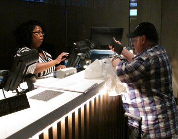 In this June 27, 2019 photo, a clerk takes a bet from a gambler at the new sportsbook at Bally's casino in Atlantic City, N.J. New Jersey surpassed Nevada in terms of sports betting volume in May, taking the national lead for the first time. (AP Photo/Wayne Parry)