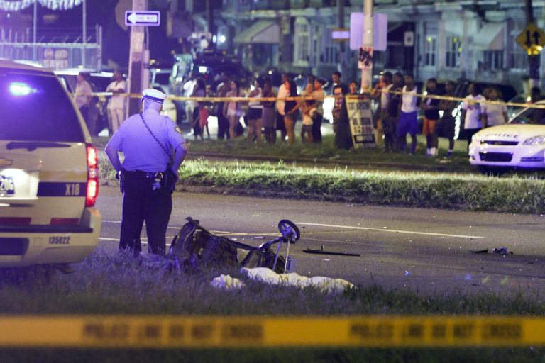 A police officer stands by a sheet covering the remains of a young child and a baby stroller at the scene of a fatal accident on Roosevelt Boulevard in the Olney section of Philadelphia on Tuesday July 16, 2013. (Joseph Kaczmarek/AP Photo)