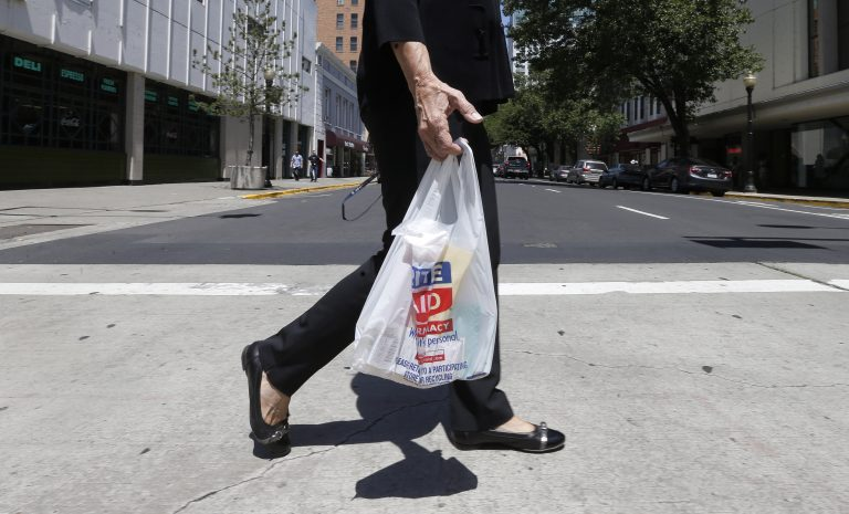 A woman walks with a plastic bag in this file photo. (AP Photo)