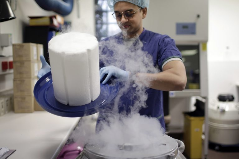 A scientist opens the lid of a cryotank containing donor sperm samples in an IVF clinic. (Wong Maye-E/AP Photo)