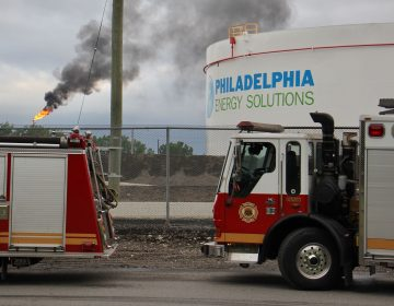 At the scene from a fire staging area under the Platt Bridge, a flare can be seen burned off fuel   (Emma Lee/WHYY)