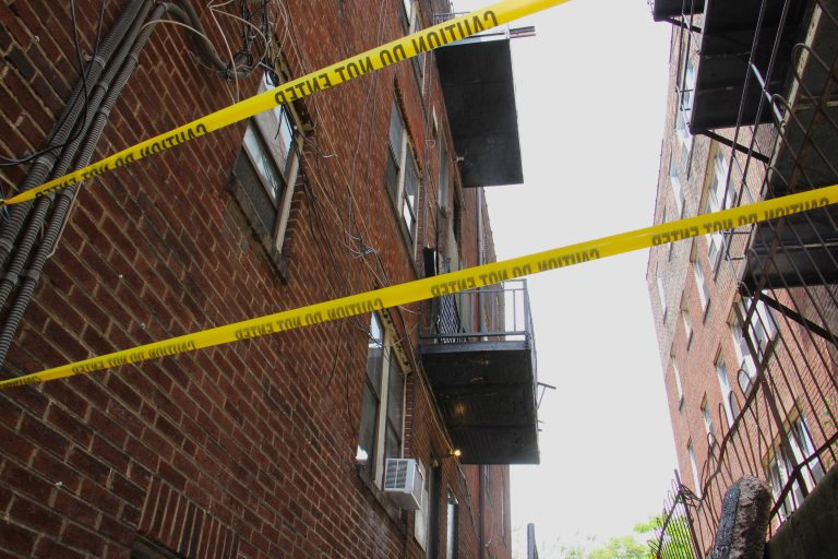 Caution tape surrounds an area at a building where a third-floor balcony collapsed, critically injuring two men. (Emma Lee/WHYY)