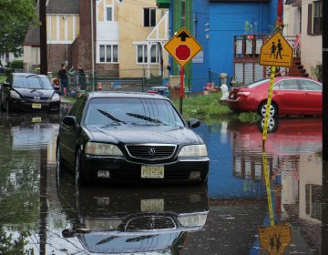 A car sits abandoned on a flooded Duncan Avenue in Westville, New Jersey. (Emma Lee/WHYY )