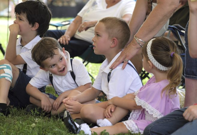 Landon Losito (left) looks over at his cousins Blaik Losito (center) and Ava Losito (right) as they sit at the side of the stage while older family members perform in the hoedown. (Matt Smith for WHYY)