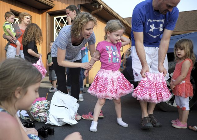 Val Rutherford (left) helps her daughter, Brenna Rutherford, put on a skirt as members of the Miller Family practice their hoedown routine. (Matt Smith for WHYY)