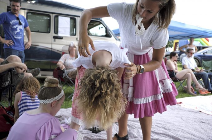 Sophie Rutherford (left) has her hair fluffed out by her aunt, Kelsea Rutherford, as they get ready for a performance of the Miller Family Hoedown. (Matt Smith for WHYY)
