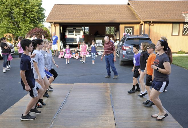 Members of the Miller family practice their hoedown routine on a portable dance floor in the driveway of the home of Lester Miller in Kutztown, Pennsylvania. (Matt Smith for WHYY)