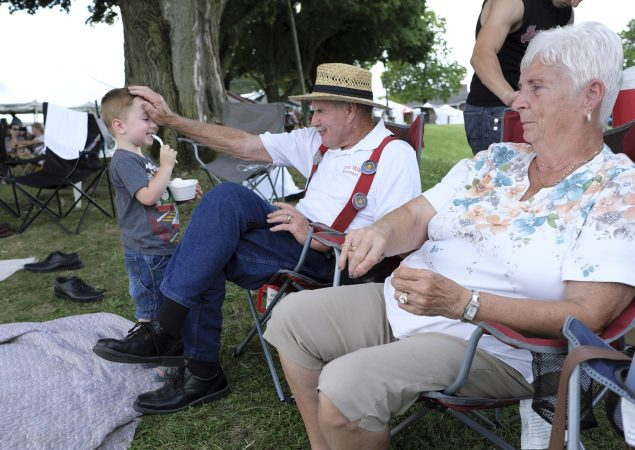 Kody Rutherford (left) interacts with his great-grandfather Lester Miller (center) and great-grandmother Faye Miller (right) as they rest between performances. (Matt Smith for WHYY)