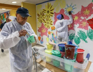 Tyrone Webb stirs green paint in a small room in Suburban Station. He's painting as part of the Same Day Work program. (Michael Bryant/Philadelphia Inquirer)