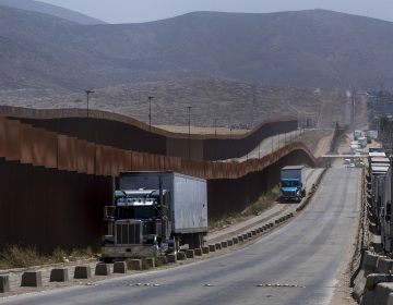 Trucks pass along a border wall as they get into position to cross into the United States at the border in Tijuana, Mexico, on Friday. Companies have been rushing to ship as many goods as possible out of Mexico to get ahead of possible tariffs threatened by President Donald Trump, hurriedly sending cars, appliances and construction materials across the border to beat Monday's deadline. (Hans-Maximo Musielik/AP)