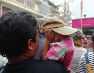 Child wear hat closing his ears for fear loud noise