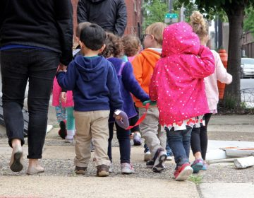 A group of children walk with their caregivers on Vine Street.  (Emma Lee/WHYY)