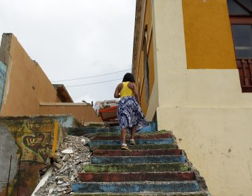 A woman walks through La Perla, a neighborhood on the edge of Old San Juan, in 2017. (AFP Contributor/Getty Images)