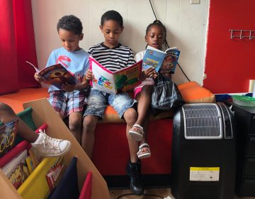 Christian Howell (center) is flanked by younger siblings Kaiden and Karima at the African Barbershop on North Market Street in Wilmington. (Cris Barrish/WHYY)