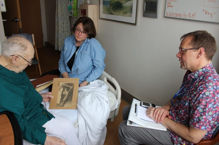 Thor Ringler (right) interviewed Ray Miller (left) in Miller's hospital room at the William S. Middleton Memorial Veterans Hospital in Madison, Wis., in April. Miller's daughter Barbara (center) brought in photos and a press clipping from Miller's time in the National Guard to help facilitate the conversation. (Bram Sable-Smith for NPR)