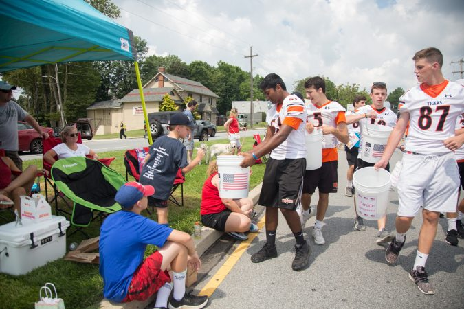 Members of the Marple Newtown High School football team walk along the parade route collecting donations to help support the annual Fourth of July parade. (Emily Cohen for WHYY)