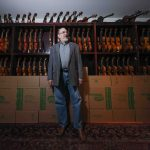 Singer-songwriter and session musician David Bromberg stands in front of a portion of his collection of violins. (Saquan Stimpson for WHYY)