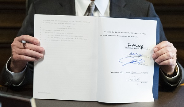 Governor Tom Wolf holding up the signed 2019-20 budget. The Commonwealth Foundation says it contains $61 million in earmarks. (Matt Rourke/AP Photo)