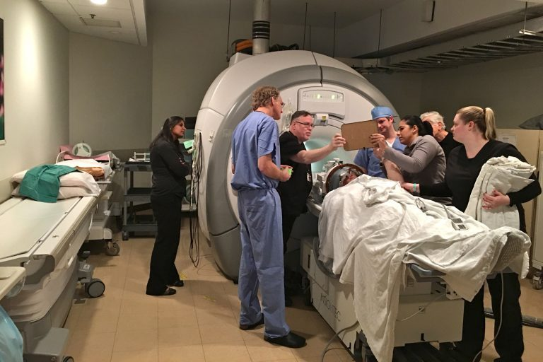 Dr. Gordon Baltuch and his team check on a patient throughout a procedure that uses a beam of ultrasound waves to stop his hand from trembling. (Kyrie Greenberg/WHYY)
