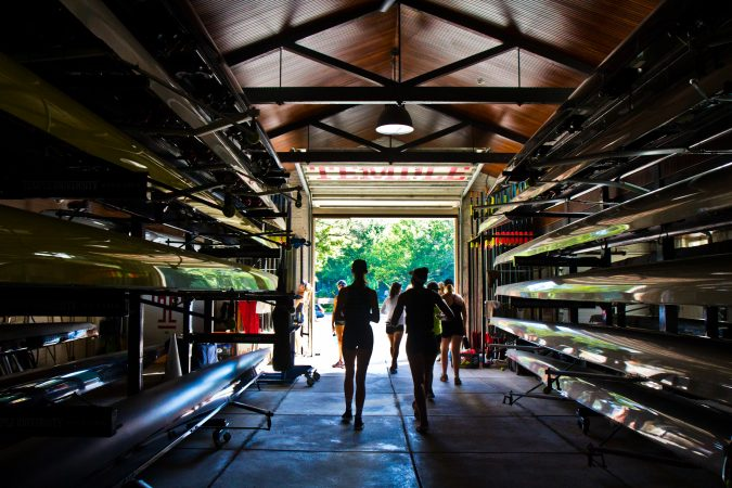 Girls 19 years and under walk through a boathouse during the Mid-Atlantic U.S. Olympic Development Program program on the Schuylkill in Philadelphia. (Kimberly Paynter/WHYY)