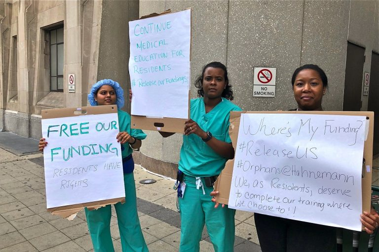 Anesthesiology residents Archana Gundigi, Rosemary De La Cruz, and Jo Linnen protest outside Hahnemann, demanding that management release their government funding to enable them to seek placements elsewhere. (Nina Feldman/WHYY)