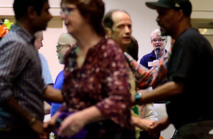 In the background Marilyn 'Zip' Warmerdam calls a 'tip' at a Center City hotel ballroom during the 36th annual LGBT Square Dance Convention. (Bastiaan Slabbers for WHYY)