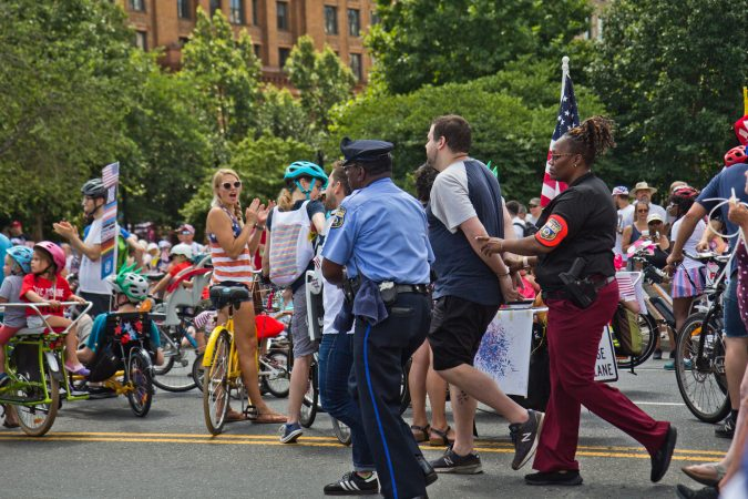 A protester demanding immigrants at the border be removed from detention centers is arrested at Philadelphia's Fourth of July Parade. (Kimberly Paynter/WHYY)