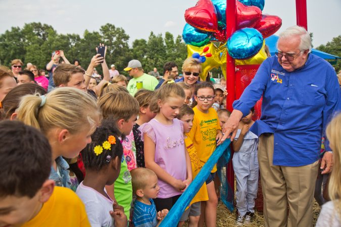 Jim and Lynn Cummings help a group of children cut the ribbon at Delran's Jake's Place. (Kimberly Paynter/WHYY)