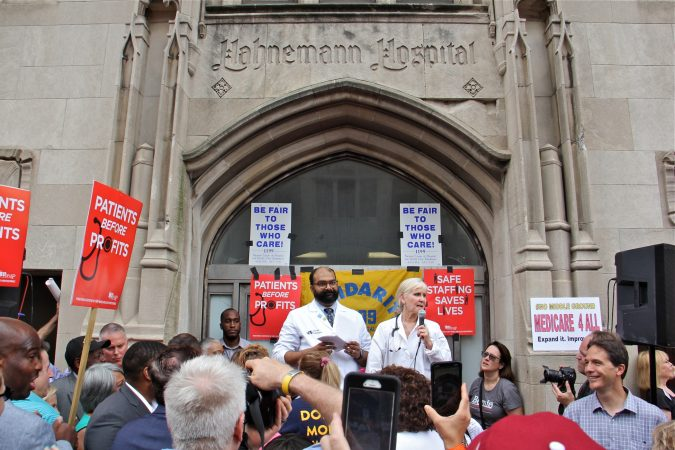 Dr. Kevin D'Mella and Dr. Rene Rothstein-Rubin address a crowd gathered to protest the closing of Hahnemann Hospital. (Emma Lee/WHYY)