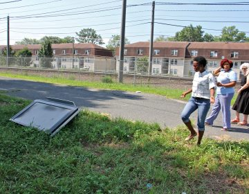 A discarded television lies in a vacant lot off Pershing Street near the PATCO rail tracks. Activists (from left) Vedra Chandler, Meishka Mitchell and Noreen Scott Garrity, are working to stop the practice of illegal dumping on Camden lots. (Emma Lee/WHYY)