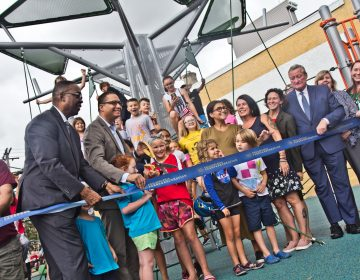 Government officials and Fishtown children cut the ribbon on Fishtown Recreation Center's new playground. (Kimberly Paynter/WHYY)