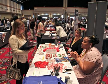 Stephanie Burton (right) of the Dialysis Center of Philadelphia, recruits nurses during the Hire Hahnemann career fair put on by Philadelphia Works at the Pennsylvania Convention Center. (Emma Lee/WHYY)